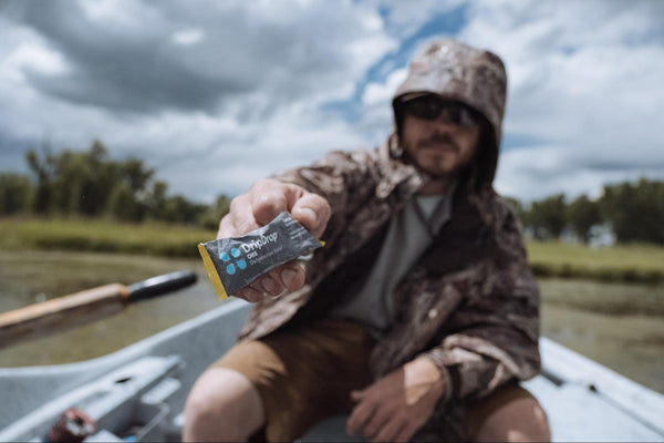 Man holding a sachet of DripDrop ORS while in a boat