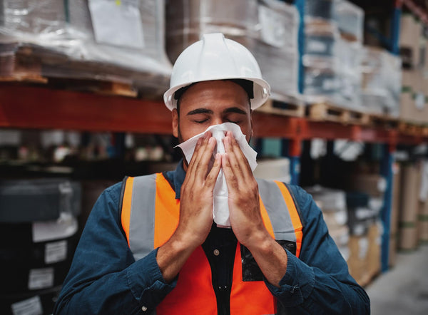 environmental allergies: hard hat worker wiping his nose