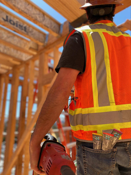 Construction worker at a jobsite with three sachets of DripDrop ORS in his back pocket