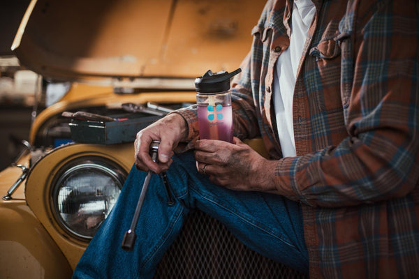 hydration definition: Male auto mechanic holding a tumbler with DripDrop ORS