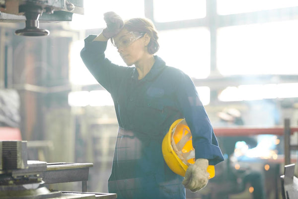 hypertonic dehydration: factory worker touching her forehead