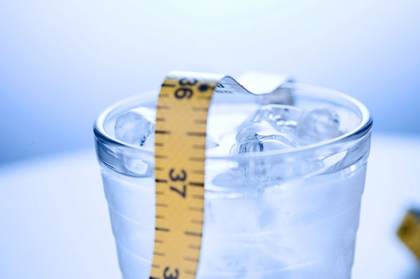 how to lose water weight: glass of cold water with a tape measure on top