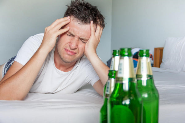 does alcohol dehydrate you: Man with hangover with bottles of beer on top on bed
