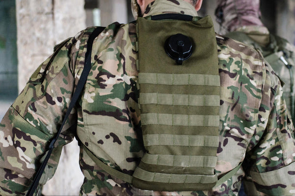 Male soldier wearing a hydration pack on his back