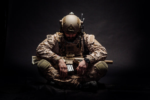 can dehydration cause depression: soldier sitting down on the ground with a gun on his lap