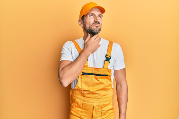 how to get rid of itchy throat: man in orange overalls touching his throat