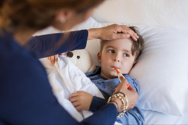 flu dehydration: Sick child lying in bed while his mother checks his temperature
