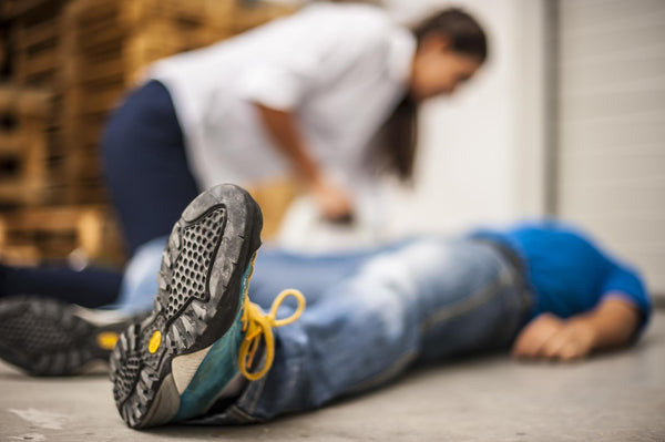 man lying on the floor with a woman applying first aid