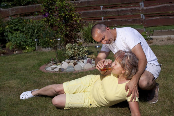first aid for dehydration: man helping the old woman to drink