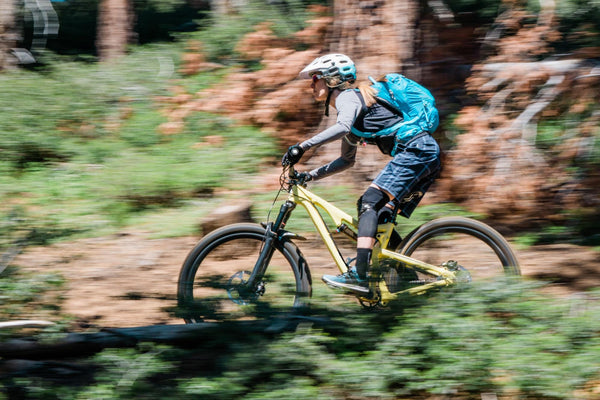 hydration pack: Woman riding a bike in the forest