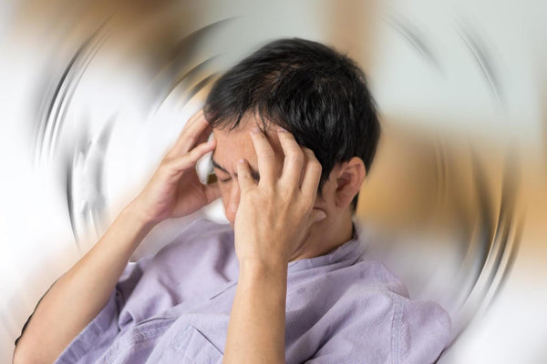 Lightheadedness and fatigue: Man with hands on his head feeling dizzy