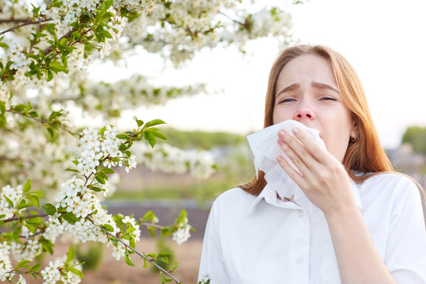 environmental allergies: woman sneezing into a tissue
