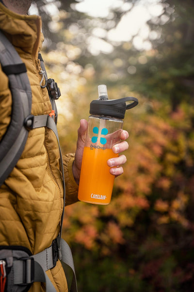 Man holding a tumbler filled with DripDrop ORS while outdoors