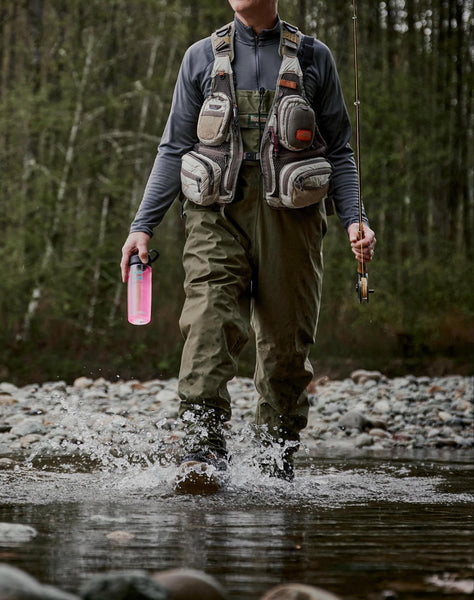 Man holding DripDrop tumbler while crossing a river