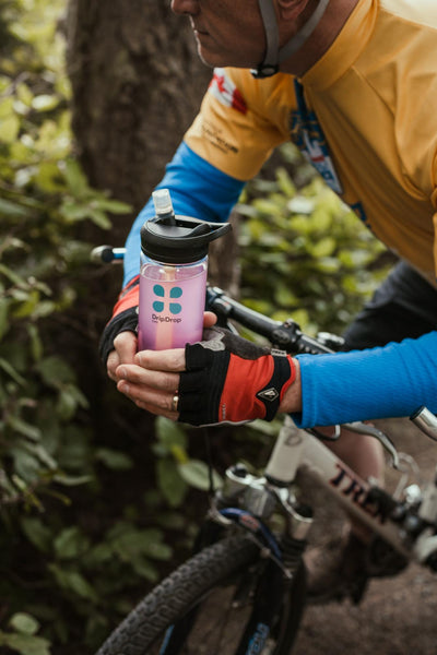 hydration definition: Male cyclist holding a tumbler with DripDrop ORS