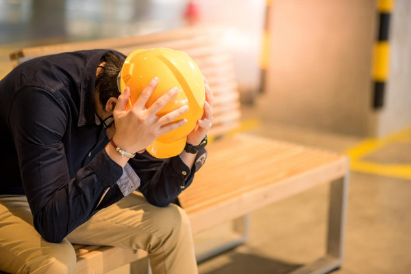 dehydration and anxiety: Man holding his head in his hands while sitting on a bench