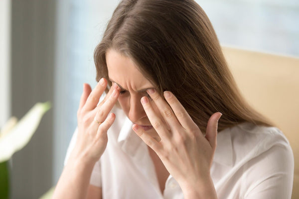 pots symptoms: woman holding her forehead with signs of headache