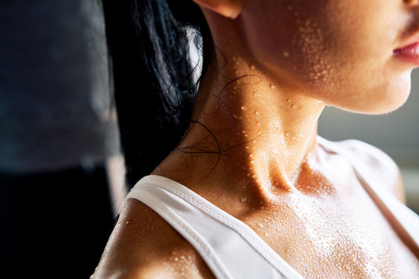 Is sweating good for you: Woman sweating in white tank top