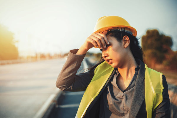 Is sweating good for you: Female construction worker wipes sweat from forehead