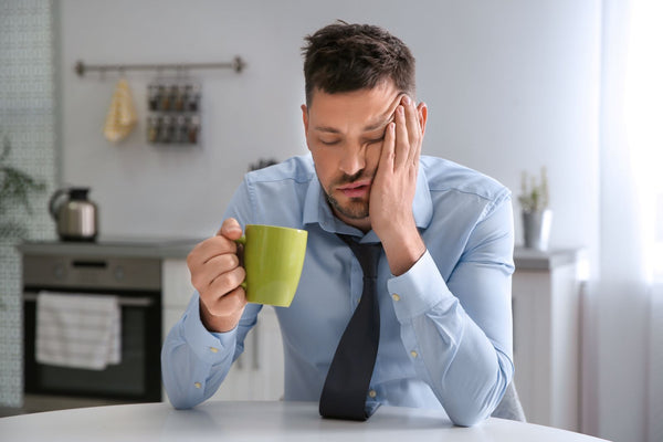 Does tea dehydrate you: Tired man drinking tea in an office