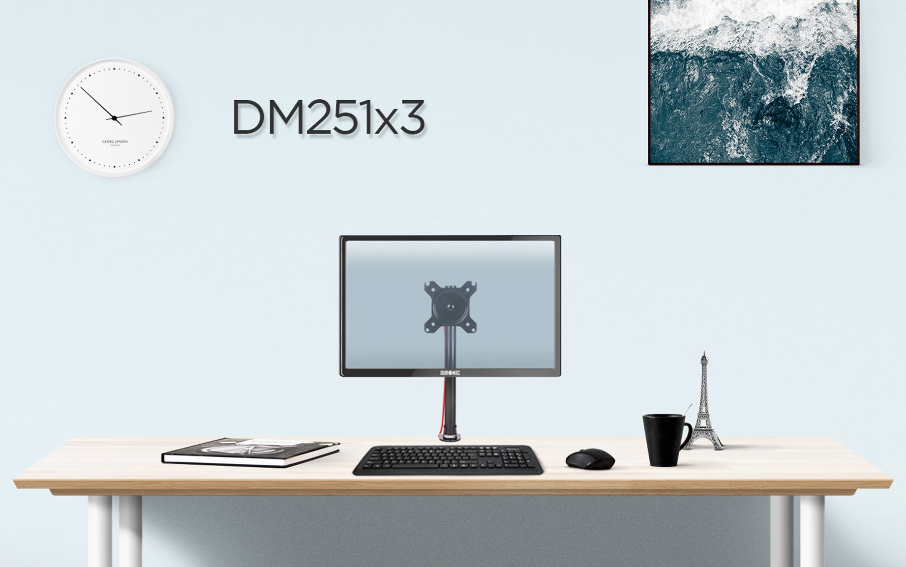 DM251X3 monitor stand on desk top surface, surrounded by office accessories.