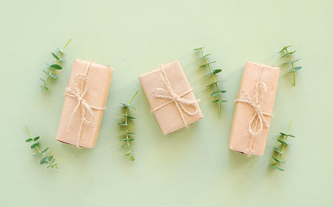 three gifts wrapped in kraft paper on a green background with stems of eucalyptus. zero waste gift inspiration from scoop marketplace