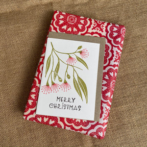Hand printed Gum Blossoms Christmas card and envelope on top of a wrapped present. The card reads 'Merry Christmas'