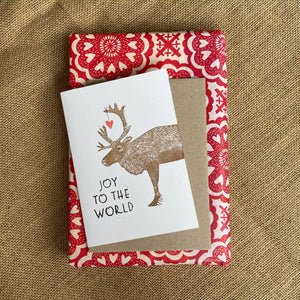 Hand printed reindeer card and envelope on top of wrapped present. The card reads 'Joy to the World'.