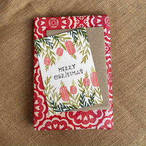 Hand printed Christmas card featuring native Australian Bottle Brush flowers on top of a wrapped present