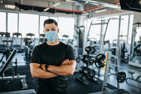 man crossing arms with mask in gym
