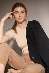 Woman sitting in beige clothing and a black blazer