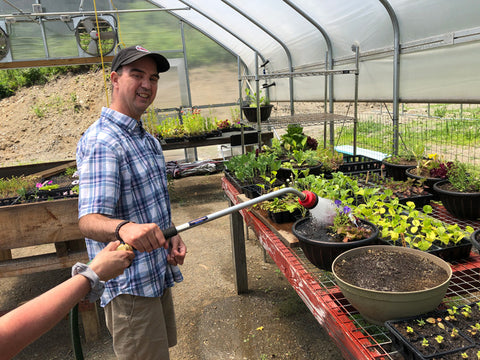 Participant in the Vocational Agriculture program waters plants in the Cultivating Dreams greenhouse