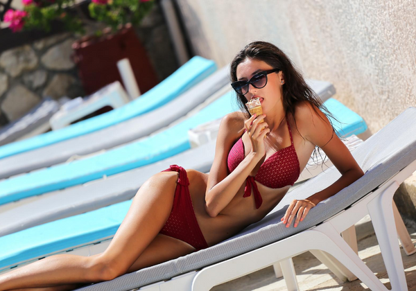 Woman Eating Chocolate Vanilla Ice Cream Cone By The Pool