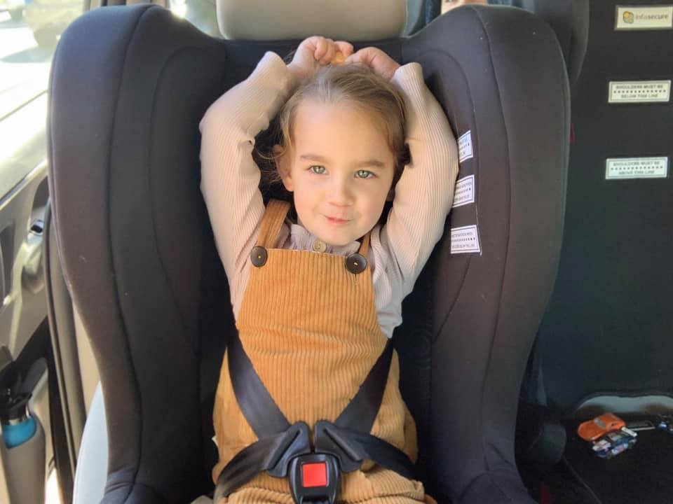 Child escaping car seat harness