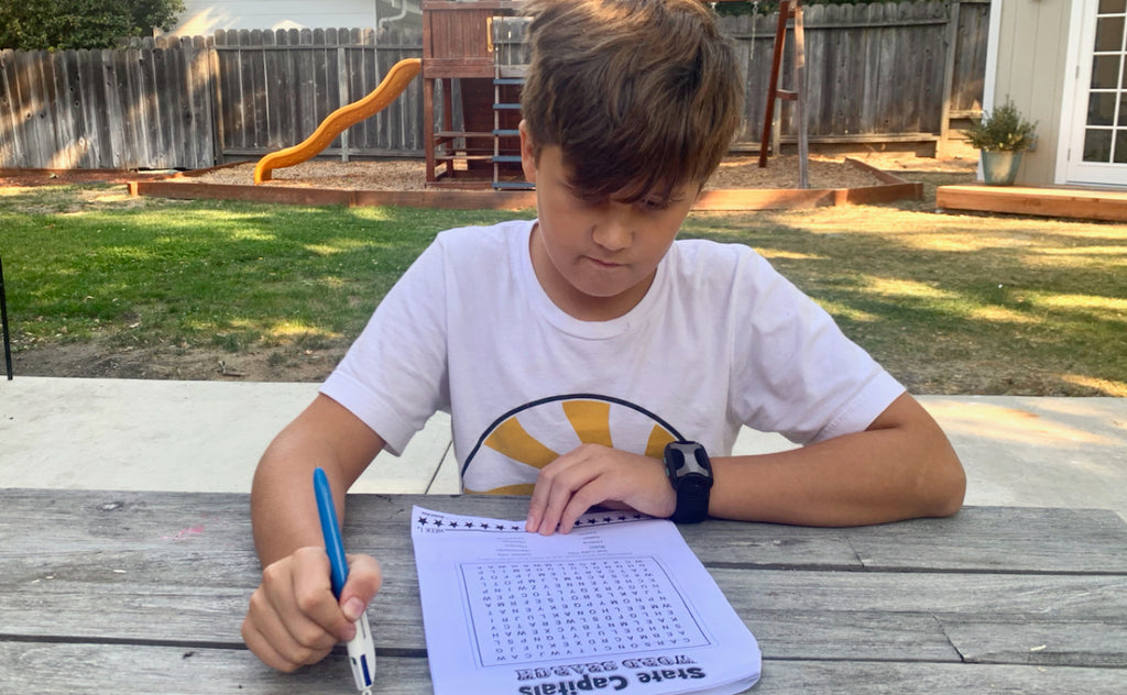 Boy filling out a word search puzzle