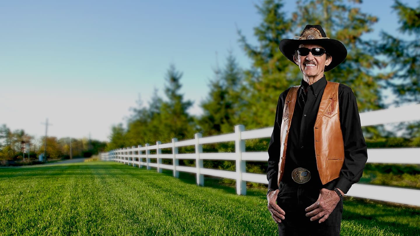 Richard Petty in front of a fence