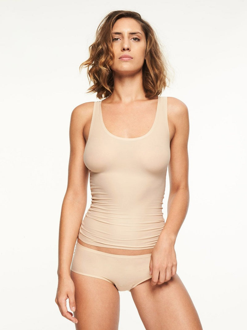 Nude colour. The smooth Tank Top from the award winning Soft Stretch Collection adds ease to everyday with high performace elasticity that is engineered to last. Wear alone or layered for a lightweight, luxe look. Relaxed one size fit for variety of shapes Scoop-neck silhouette Stays in place throughout the day