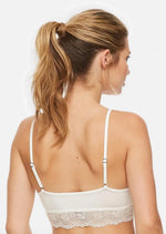 This shows the back view of the bralette. She's wearing the ivory coloured Montelle BodyBliss Breeze Bralette. The perfect bralette for sleeping or layering! Made of supremely soft, featherlight and ecologically sourced fabric, our BodyBliss Bralette has a pretty lace trim along the top and bottom. Wear it on its own as a sleep bralette or over your favorite bra when you want additional coverage.