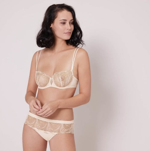 Simone Perele Sheer Embroidered Demi Cup in pearl colour. This stunning French bra highlights two of our favorite things: embroidery and that iconic demi shape.  Together they make for a show-stopping bra that hugs curves to perfection, with ultra-smooth microfiber sides and elegant two-way spaghetti straps.