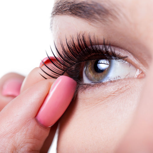 woman applying false lashes by hand