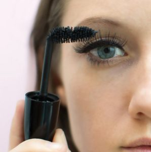 woman holding bent mascara brush up to face