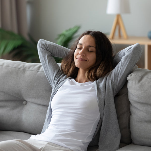 Woman relaxing on her couch with her arms back
