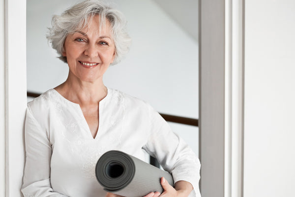 Bone health and exercise: elderly lady holds yoga mat