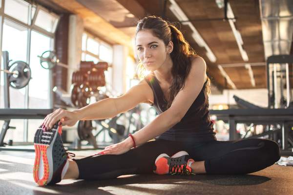 Woman stretching in a gym to avoid muscle fatigue