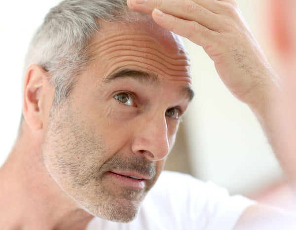 Man with gray hair experiencing hair falling out
