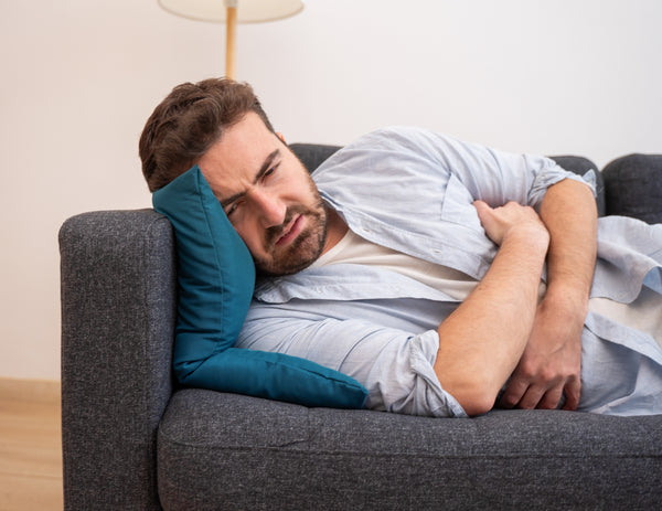 man lying down in pain on a sofa