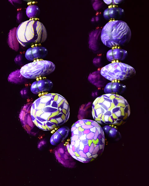 Detail fo handcrafted purple patterned rounds of polymer