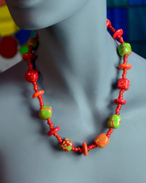 Red and green Kazuri beads, each handmade and hand painted