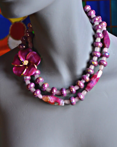 necklace with a large mauve flower and two strands of shiny and colorful pink tourmaline cylinders