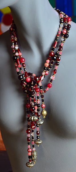 Six strands of cranberry colored glass beads in all shapes